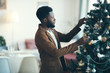 Leinwanddruck Bild - Side view portrait of modern African-American man decorating Christmas tree at home, copy space