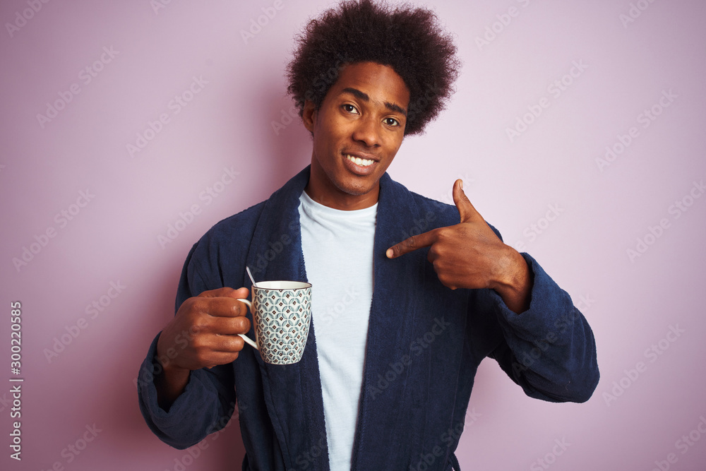 Fototapety, obrazy: Afro american man wearing pajama drinking coffee standing over isolated pink background with surprise face pointing finger to himself