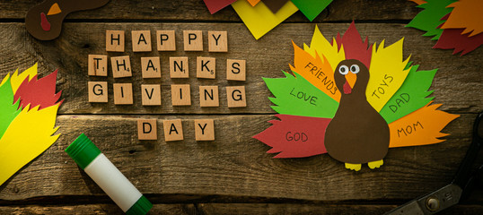 Thanksgiving paper craft - thanksful turkey on wood background, top view