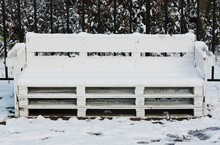 White Wooden Bench In The Snow...