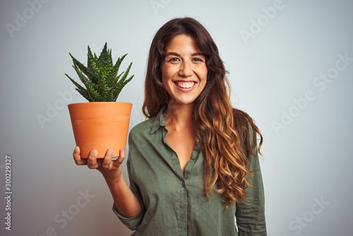 Fotografía  Young beautiful woman holding cactus pot over white isolated background with a h