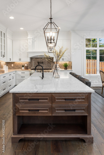 Fototapeta Beautiful kitchen in new traditional style luxury home, with quartz counters, hardwood floors, and stainless steel appliances obraz
