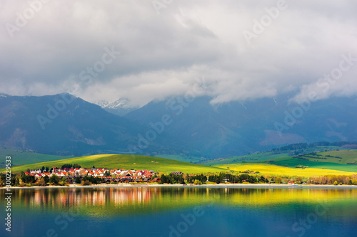 village on the shore of a lake. beautiful rural landscape in mountains. distant snow covered peaks in clouds. amazing scenery of liptovska mara water reservoir in slovakia