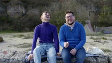 Two Gay Guys From The LGBT Community Are Sitting On A Stone Pier In A Sweater And Sweatshirt, Blue And Laughing, After Which One Puts His Head On The Shoulder Of The Other