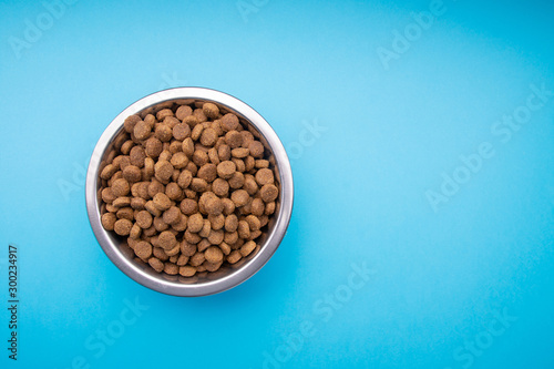 Photo  Dog food in a metal bowl. Blue background