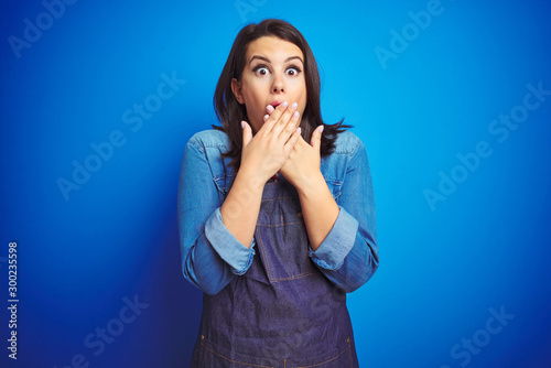 Young beautiful business woman wearing store uniform apron over blue isolated background shocked covering mouth with hands for mistake Canvas-taulu