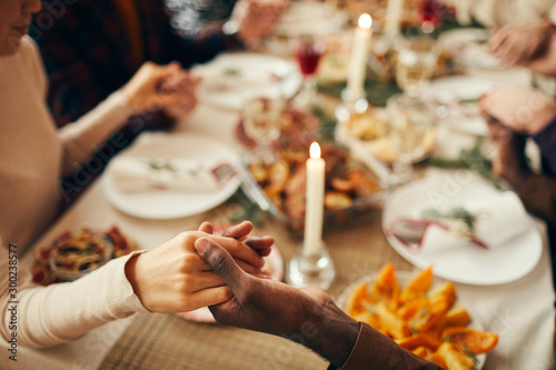 Fotomural  Closeup of people sitting at dining table on Christmas and joining hands in pray
