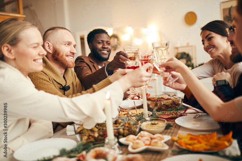 Obraz Multi-ethnic group of people raising glasses sitting at beautiful dinner table celebrating Christmas with friends and family, copy space fototapeta, plakat