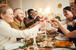 canvas print picture - Multi-ethnic group of people raising glasses sitting at beautiful dinner table celebrating Christmas with friends and family, copy space