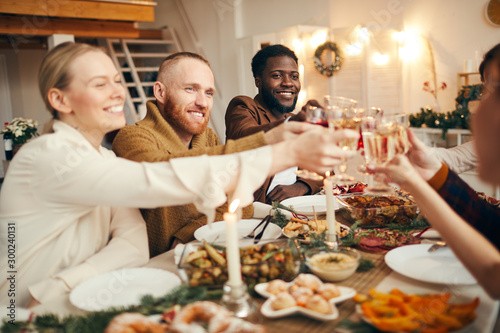 Fotomural  Multi-ethnic group of people raising glasses while celebrating Christmas with fr