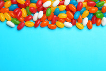 Tasty Colorful Jelly Beans On Blue Background, Flat Lay. Space For Text