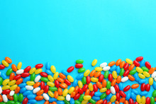 Colorful Jelly Beans On Turquoise  Background, Flat Lay. Space For Text