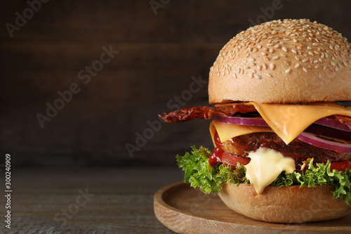 Plate with juicy bacon burger on wooden table. Space for text