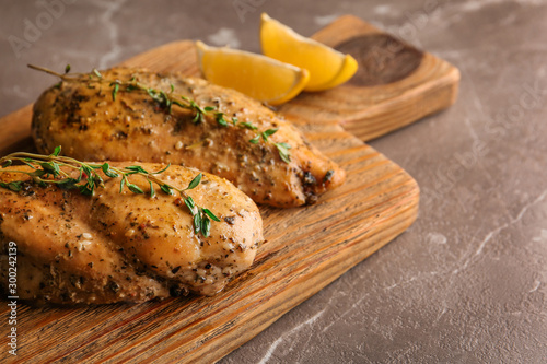 Baked lemon chicken with thyme served on grey marble table. Space for text