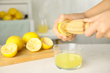 Woman squeezing lemon juice with reamer at white wooden table, closeup. Space for text