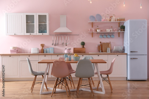 Carta da parati Stylish kitchen interior with dining table and chairs