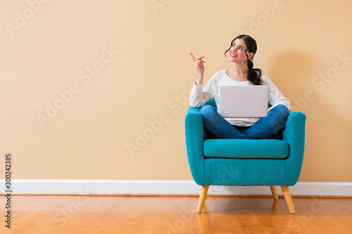 Fotografía Young woman with a laptop computer pointing something sitting in a chair