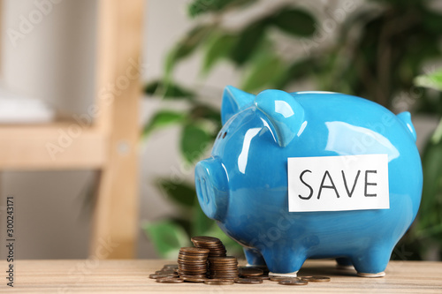 Fotografía  Piggy bank with word SAVE and coins on wooden table against blurred background