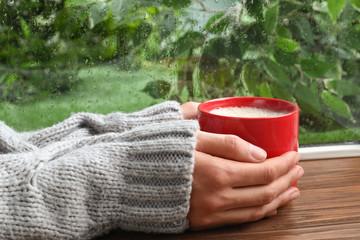 Woman with cup of coffee near window on rainy day, closeup