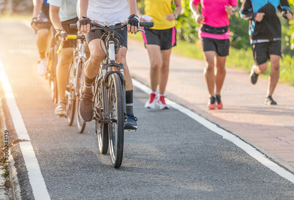 Fototapety, obrazy: Close up movement group of cyclists during ride bicycle with male runner jogging for exercise on the road park in sunset time healthy lifestyle concept