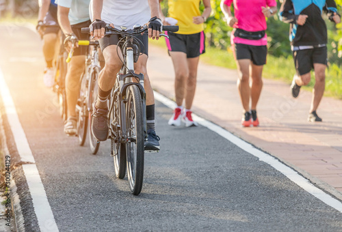 Photo sur Aluminium Jogging Close up movement group of cyclists during ride bicycle with male runner jogging for exercise on the road park in sunset time healthy lifestyle concept