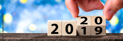 Poster Pierre, Sable Hand Changing Date From 2019 To 2020 On Wooden Cube Calendar / New Year's Concept