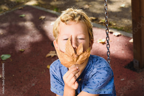 Fototapeta  Portrait of 6 year old blond boy with hiding his face with a leaf