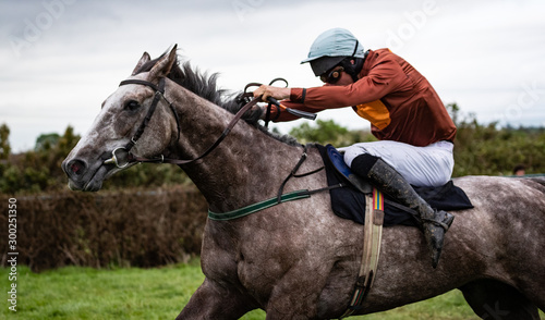 Stampa su Tela Close up on sprinting race horse and jockey on the race track