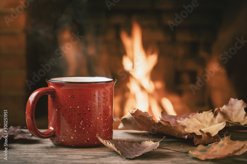 Photo sur Aluminium Cafe Red mug with hot tea in front of a burning fireplace, comfort and warmth of the hearth concept