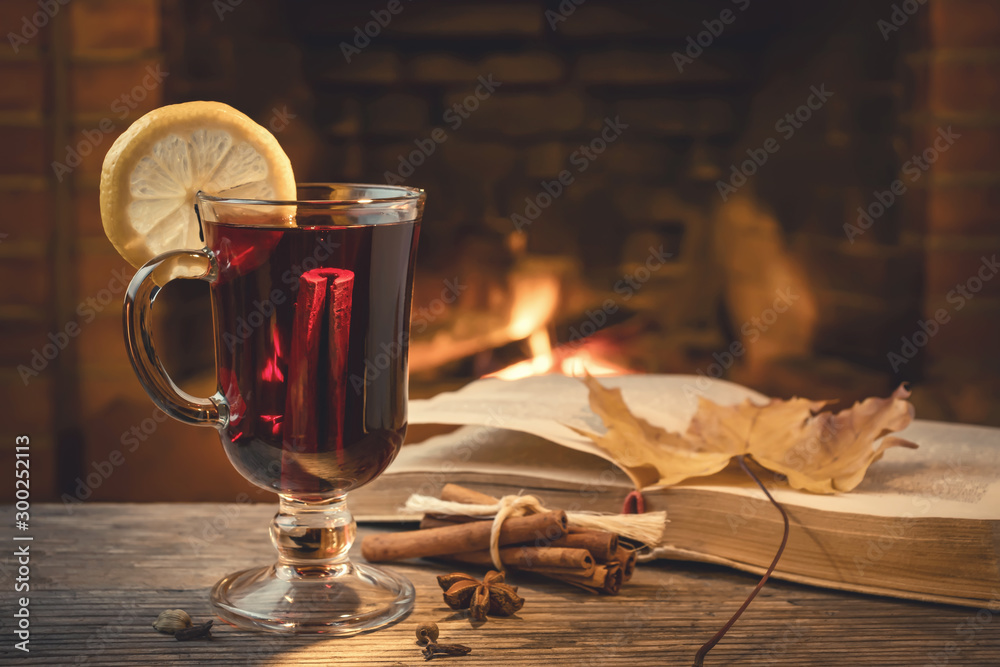 Fototapeta Glass of mulled wine, spices, a book on a table in a cozy room with a burning fireplace