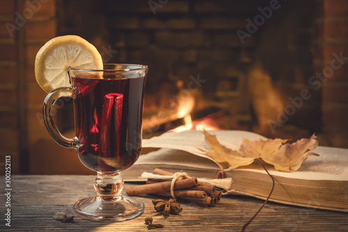 Obraz Glass of mulled wine, spices, a book on a table in a cozy room with a burning fireplace - fototapety do salonu