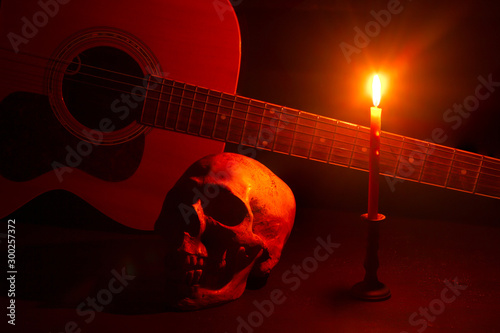 Fotomural Human skull and guitar in candlelight on a wooden table