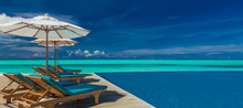 Deck Chairs With Umbrellas At Maldives Resort With Infinity Pool And Beach