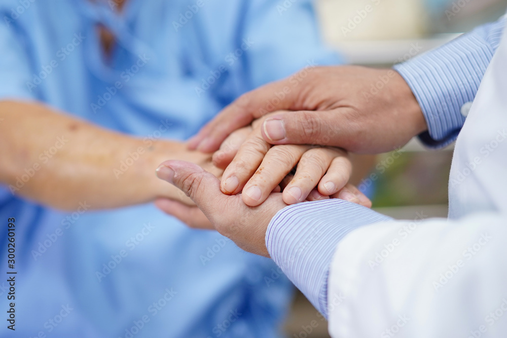 Fototapeta Holding Touching hands Asian senior or elderly old lady woman patient with love, care, helping, encourage and empathy at nursing hospital ward : healthy strong medical concept .