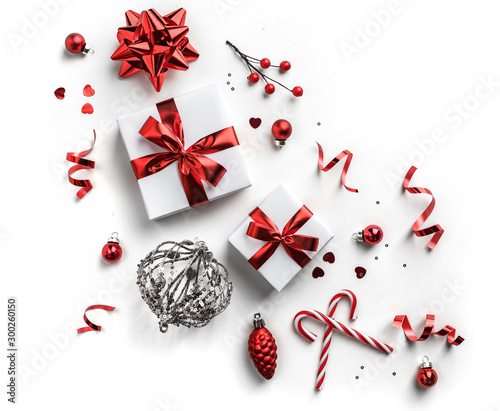 Photographie  Christmas decoration, gift boxes with red ribbon, sparkles, confetti, christmas candy and balls on white background