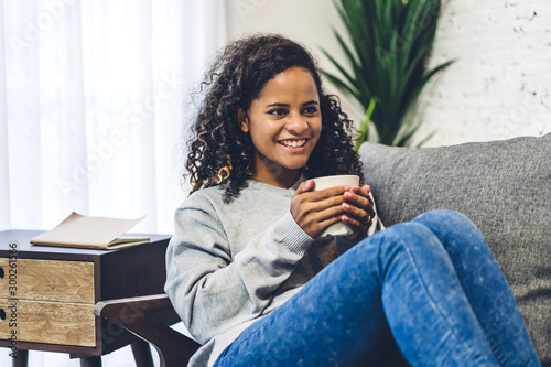 Foto auf Leinwand Tee Young african american black woman relaxing drinking cup of hot coffee or tea on couch at home