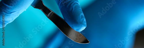 Fotografia  Surgeon arms in sterile uniform holding sharp knife