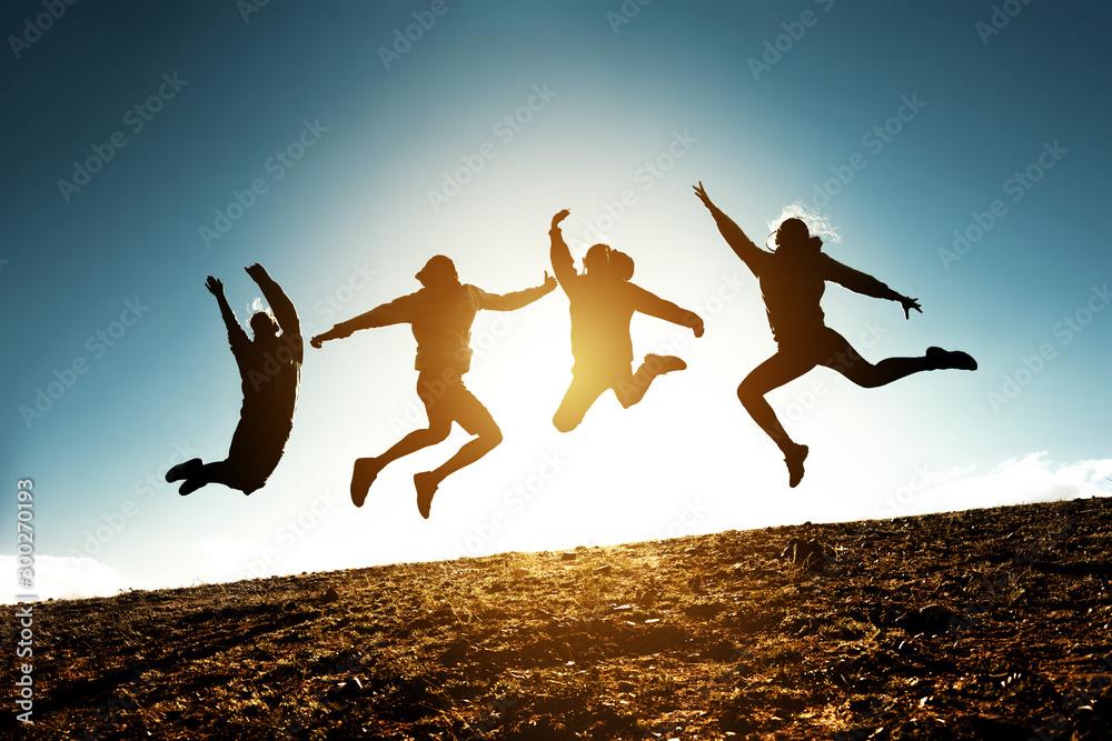 Fototapeta Four jumping silhouettes friends against sun