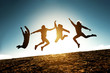 canvas print picture - Four jumping silhouettes friends against sun