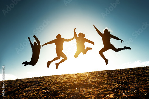 Photo Four jumping silhouettes friends against sun