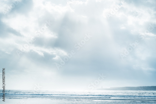 Foto op Aluminium Wit Beach and sea with cloudy sky and sunbeams.