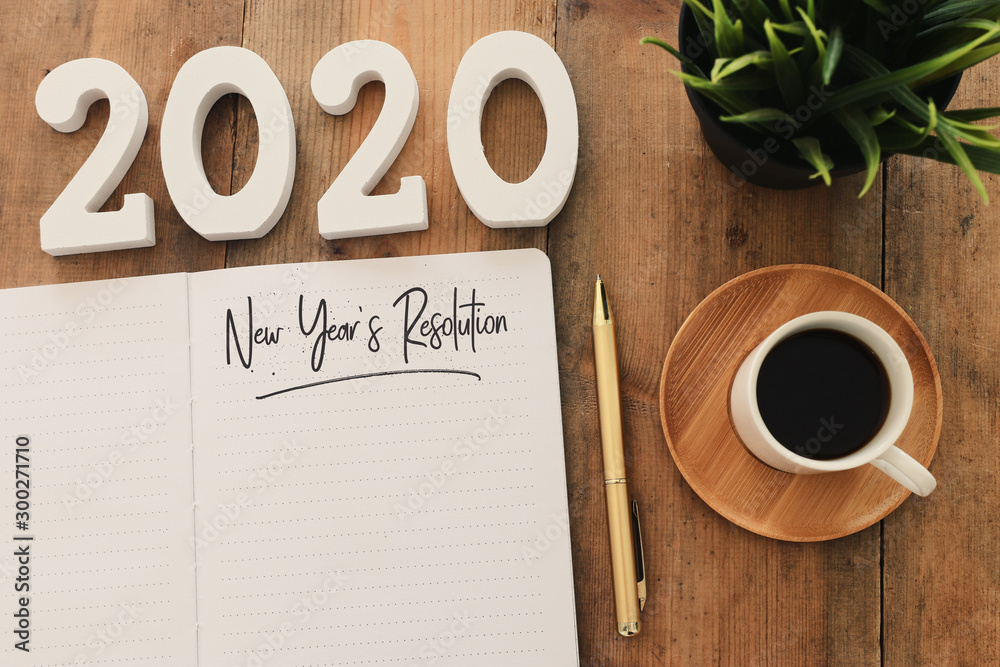Fototapeta Business concept of top view 2020 year's resolution list with notebook, cup of coffee over wooden desk