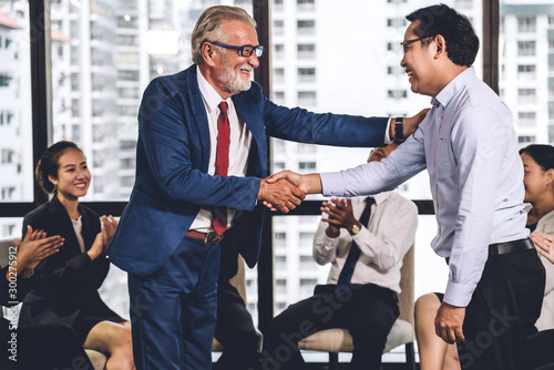 Pinturas sobre lienzo  Image two business partners in elegant suit successful handshake together standing in front of group of casual business clapping hands in modern office