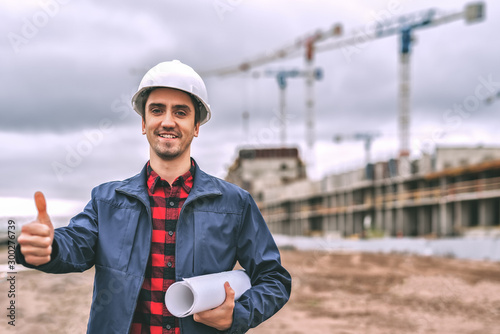 Valokuva civil engineer in a white helmet on the background of construction, with a raised thumb