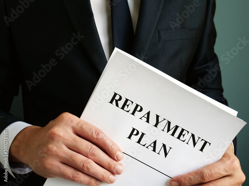 Photo sur Toile Nature Repayment Plan that the man holds.