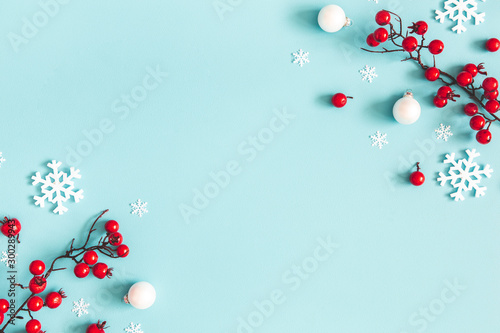Poster Fleur Christmas or winter composition. Snowflakes and red berries on blue background. Christmas, winter, new year concept. Flat lay, top view, copy space