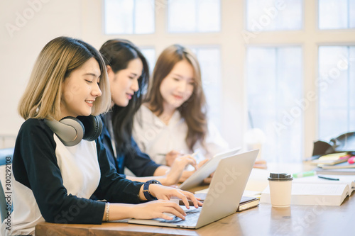 Photo College students studying with laptop  while sitting at table inthe library