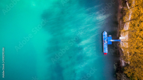 Foto auf Leinwand Reef grun Emerald Green Lake with Colorful Boat. Aerial Drone Top Down Photo.