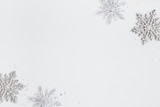 Fototapeta Kawa jest smaczna - Christmas or winter composition. Frame made of silver snowflakes on pastel gray background. Christmas, winter, new year concept. Flat lay, top view, copy space