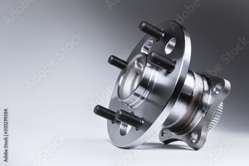 Fototapeta New Wheel hub assembly with bearing. This is part of the car suspension on a gray background with a gradient. The concept of new car parts obraz